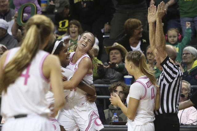 Oregon's Ruthy Hebard, center left, hugs Sabrina Ionescu, as Jaz Shelley, right, watches after Ionescu made a 3-point shot at the buzzer to end the third quarter of the team's NCAA college basketball game against Arizona in Eugene, Ore., Friday, Feb. 7, 2020. (AP Photo/Chris Pietsch)