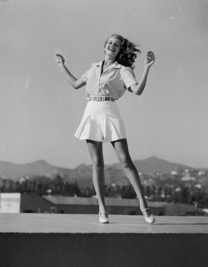 <p>Rita Hayworth poses for a publicity still for <em>You'll Never Get Rich </em>wearing pleated shorts and a short-sleeve blouse.</p>