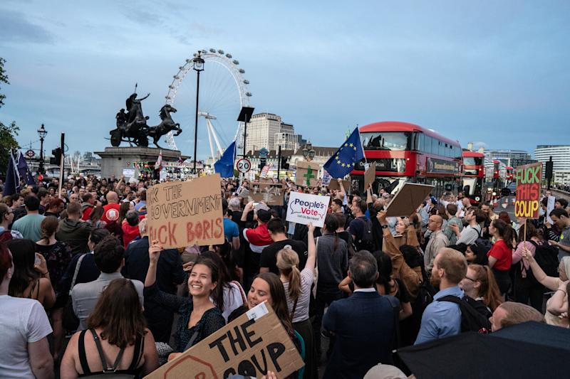 Hundreds of people are seen protesting against Boris Johnson outside the houses of parliament on Westminster bridge