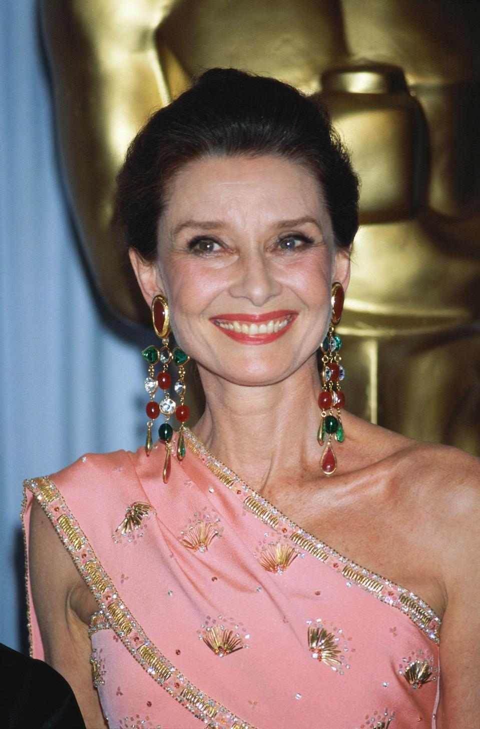On hand to present the awards for achievement in costume design, Audrey Hepburn dazzled into a custom pink gown by Hubert de Givenchy. The bold color was complemented by a pair of chandelier earrings featuring a mix of precious stones set in gold.