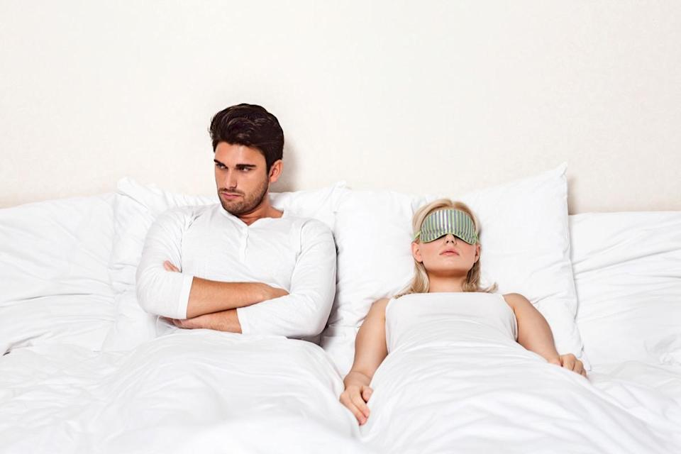 Angry young man with woman sleeping in bed