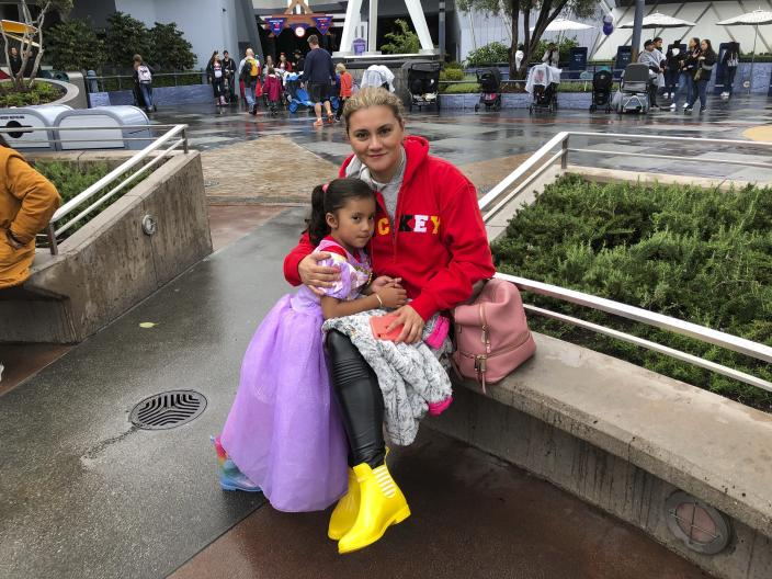 Andrea Vizcarra and her 4-year-old daughter Maria Jose here on a family vacation from Mexico but their plans were upended when Disney and Universal closed, at Disneyland in Anaheim, Calif. on Friday, March 13, 2020. They were going to see their two-day trip cut short and raced over to the park late Thursday to try to maximize their time there. Disneyland is closing its doors for the rest of the month, shuttering one of California's best-known attractions as the state hurries to stop the spread of the coronavirus. (AP Photo/Amy Taxin)