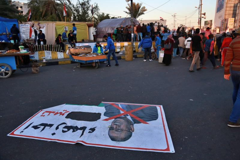 "In this Wednesday, Dec. 18, 2019 photo, a poster with a defaced photo of Qusay al-Suhail, a candidate for the prime minister's post, and Arabic that reads, ""one of the leaders of the destruction,"" is lying on the ground in Tahrir Square, Baghdad, Iraq. Thousands of protesters poured into the streets of Baghdad and Iraq's southern provinces on Sunday, rejecting the nomination of what some call an Iran-backed candidate for the prime minister's post. The demonstrations came as a midnight deadline loomed without a solution being reached to name an interim premier. (AP Photo/Khalid Mohammed)"