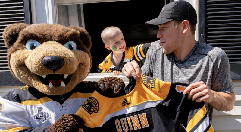Boston's Charlie Coyle (right) poses with the Bruins' mascot Blades (left) and three-year-old Quinn Waters (centre). (Twitter//@NHLBruins)