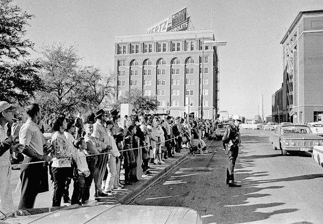 <p>The street across from the Dallas criminal courts building on Nov. 23, 1963, which houses the county jail, is lined with people hoping for a glimpse of Lee Harvey Oswald, accused of assassinating President John Kennedy, should he be moved from the city jail. The building is near the one, background, from which the fatal shots were fired. (Photo: AP) </p>