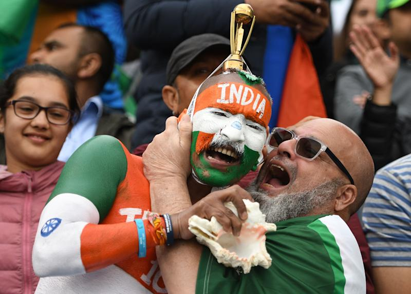 Indian supporters celebrate in the crowd during the 2019 Cricket World Cup group stage match between India and Pakistan at Old Trafford in Manchester, north-west England, on June 16, 2019. (Photo by Oli SCARFF / AFP) / RESTRICTED TO EDITORIAL USE (Photo credit should read OLI SCARFF/AFP/Getty Images)