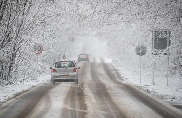 A car makes its way along a snow-covered A252 near to Charing in Kent