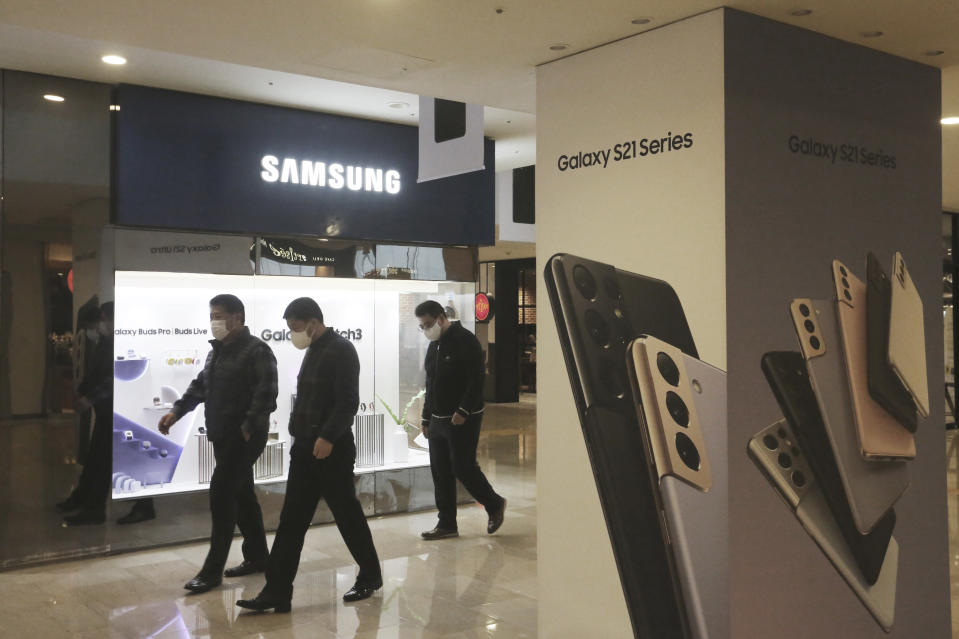 People pass by an advertisement of Samsung Electronics' Galaxy S21 Series smartphones at its shop in Seoul, South Korea, Thursday, Jan. 28, 2021.Samsung Electronics Co. said Thursday its operating profit for last quarter rose by more than 26% as it capped off a robust business year where its dual strength in parts and finished products allowed it to thrive amid the pandemic. (AP Photo/Ahn Young-joon)
