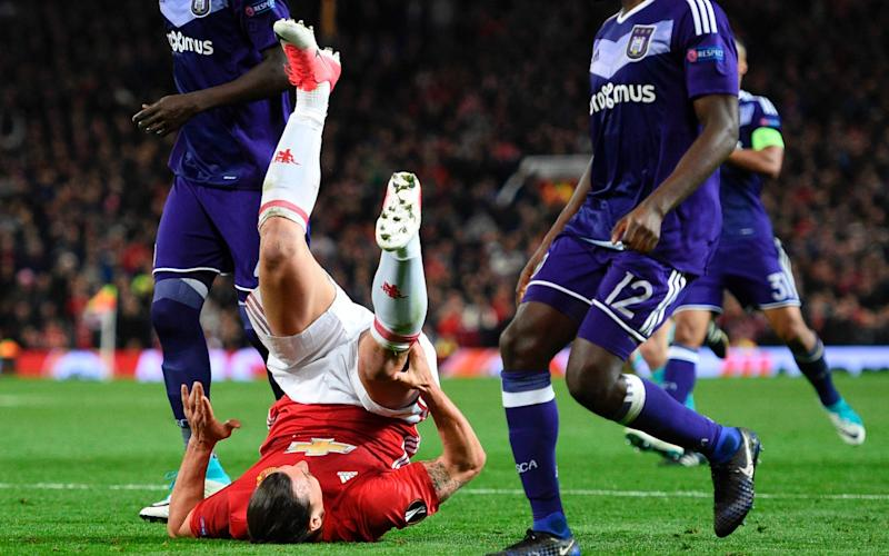 Ibrahimovic, here clutching his knee during last week's Europa League clash, faces a long spell out - AFP