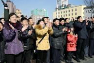 """North Koreans watching a huge screen broadcasting an official announcement that the country """"successfully"""" put an Earth observation satellite into orbit, calling it an """"epoch-making"""" achievement, applaud in Pyongyang, North Korea, in this photo released by Kyodo February 7, 2016. REUTERS/Kyodo"""