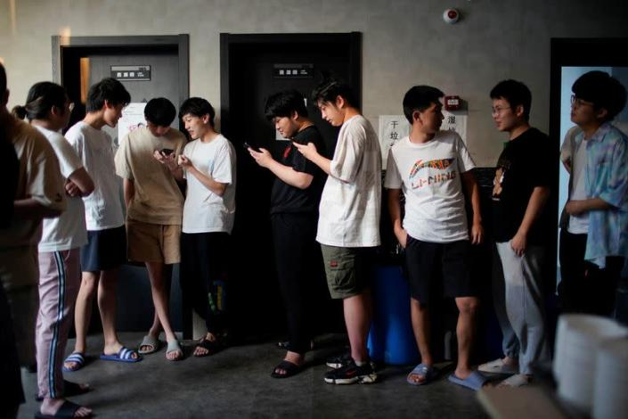 Players of Rogue Warriors esports team take a break before their dinner, in a cafeteria at their club in Shanghai