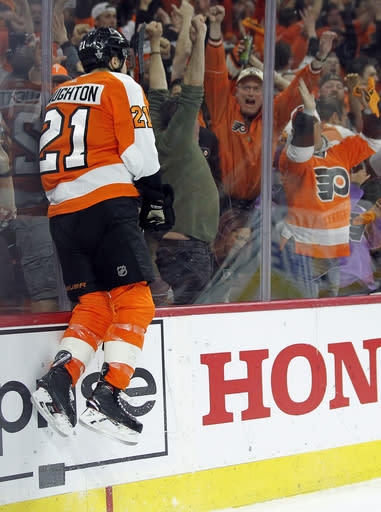 Philadelphia Flyers' Scott Laughton jumps against the glass to the cheers of the fans after scoring a goal on a breakaway during the second period in Game 6 of an NHL first-round hockey playoff series against the Pittsburgh Penguins, Sunday, April 22, 2018, in Philadelphia. (AP Photo/Tom Mihalek)