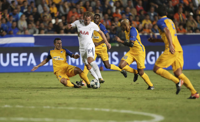 Tottenham's Harry Kane, second left, who scored three goals against APOEL goes with the ball between APOEL's players during the end of the Champions League Group H soccer match between APOEL Nicosia and Tottenham Hotspur at GSP stadium, in Nicosia, Cyprus, on Tuesday, Sept. 26, 2017. Tottenham won 3-0.(AP Photo/Petros Karadjias)
