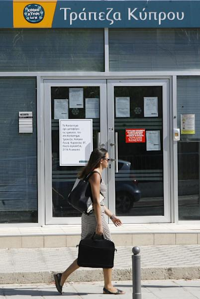 A woman walks outside a branch of Bank of Cyprus in Nicosia, Monday, July 29, 2013. Cyprus' government says depositors at the bailed-out country's largest lender will lose a total of 47.5 percent of their savings over 100,000 euros. Losses were initially put at 37.5 percent. Another 22.5 percent remained tied up until the lender's total recapitalization needs were calculated and announced Tuesday by government spokesman Victoras Papadopoulos. The money will be used to boost the Bank of Cyprus' capital buffers. In exchange, depositors will get shares in the bank.(AP Photo/Philippos Christou)