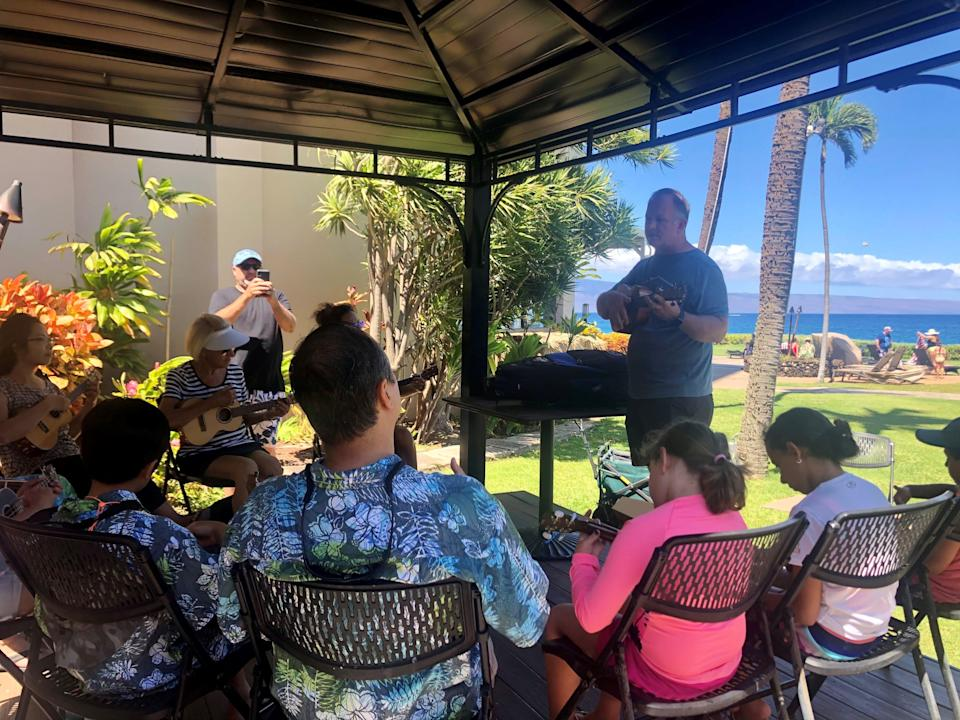 Jason Jerome, owner of Lahaina Music, teaches guests how to play the ukulele at Royal Lahaina Resort on the Hawaiian island of Maui on Monday, July 5. Jerome's business dried up during the pandemic but is starting to come back as tourists return.
