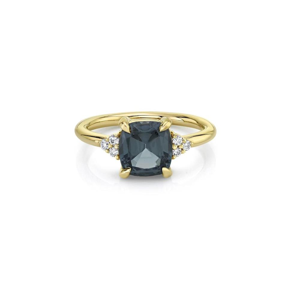 """The three white diamonds on each side of the band really make the center stone pop. The dark grey spinel may be an unlikely color of choice for an engagement ring, but the cushion setting is still a classic if you want something timeless but with a contemporary feel. $6000, Marrow. <a href=""""https://www.marrowfine.com/collections/alternative-engagement-rings/products/burmese-spinel-cushion-ring"""" rel=""""nofollow noopener"""" target=""""_blank"""" data-ylk=""""slk:Get it now!"""" class=""""link rapid-noclick-resp"""">Get it now!</a>"""