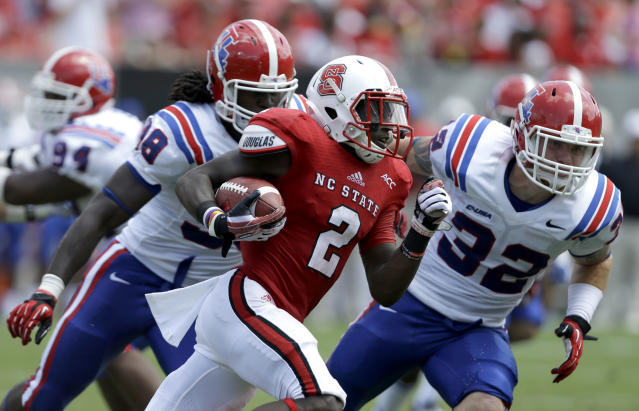 North Carolina State's Rashard Smith (2) runs the ball as Louisiana Tech's Mitch Villemez (32) and Vontarrius Dora (98) chase during the first half of an NCAA college football game in Raleigh, N.C., Saturday, Aug. 31, 2013. (AP Photo/Gerry Broome)
