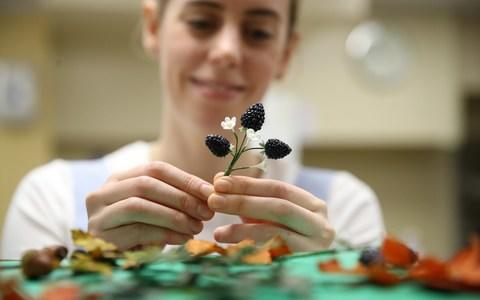 Baker Sophie Cabot puts the finishing touches to the cake decorations - Credit: Reuters