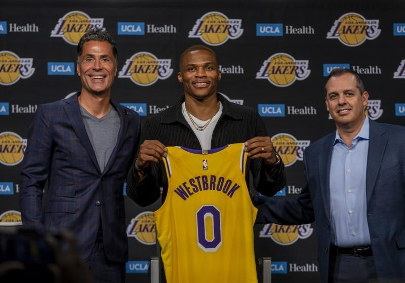 Los Angeles, CA - August 10: Russell Westbrook, center, holds up his Lakers jersey as he is introduced as one of the newest Lakers by Vice President of Basketball Operations/General Manager Rob Pelinka, left, and head coach Frank Vogel during a press conference at the Staples Center in Los Angeles Tuesday, Aug. 10, 2021. (Allen J. Schaben / Los Angeles Times)
