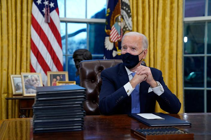 President Joe Biden waits to sign his first executive order in the Oval Office of the White House on Wednesday, Jan. 20, 2021, in Washington.