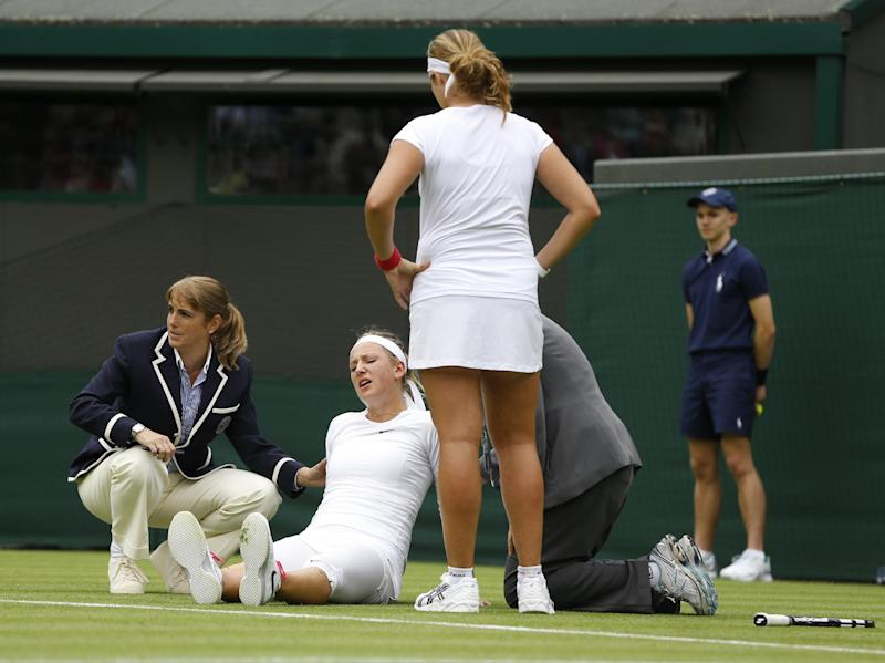 Victoria Azarenka of Belarus, second from left, is attended to after taking a fall during her Women's first round singles match with Maria Joao Koehler of Portugal, front right, at the All England Lawn Tennis Championships in Wimbledon, London, Monday, June 24, 2013. (AP Photo/Kirsty Wigglesworth)