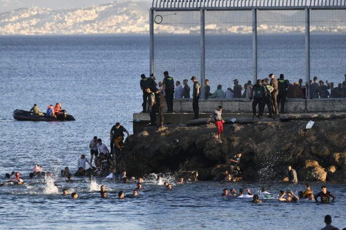 Spanish Guardia Civil officers try to stop people from Morocco swimming and entering into the Spanish territory at the border of Morocco and Spain, at the Spanish enclave of Ceuta on Monday, May 17, 2021. Authorities in Spain say that around 1,000 Moroccan migrants have crossed into Spanish territory (Antonio Sempere/Europa Press via AP)