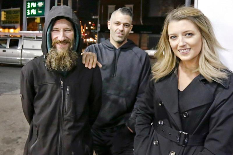 Johnny Bobbitt poses for a picture in November last year with Mark D'Amico and Kate McClure. Police raided their home on Thursday (Elizabeth Robertson/AP)