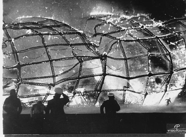 <p>The blazing inferno that was the German airship Hindenburg is reduced to ruins as a survivor, lower right hand corner, runs to safety, May 6, 1937, after it exploded on mooring at Lakehurst Naval Air Station in New Jersey. Rescuers, left and center, rush forward to pull other passenger and crew away from the fiery wreckage. (AP Photo) </p>