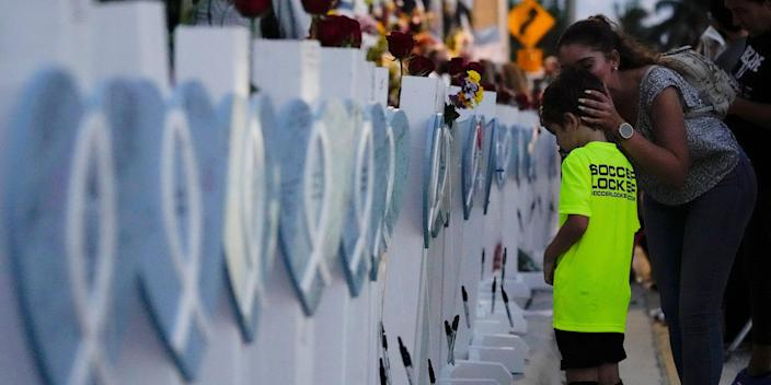 A boy stands in front of a memorial for victims of the Surfside building collapse.