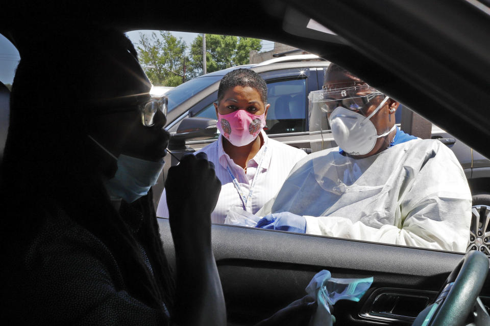 In this photo made on Monday, July 20, 2020, Kiva A. Fisher-Green, center, watches as nurse Ruth John, right, takes a sample from Walter Lewis for a COVID-19 test in the driveway of the Alma Illery Medical Center in the Homewood neighborhood of Pittsburgh. In March and April when Philadelphia and its surroundings became one of the nation's hot-spots for COVID-19 cases, Pittsburgh seemed at the time, to be under more control: the city racked up a fraction of the coronavirus cases as the other side of Pennsylvania. (AP Photo/Gene J. Puskar)