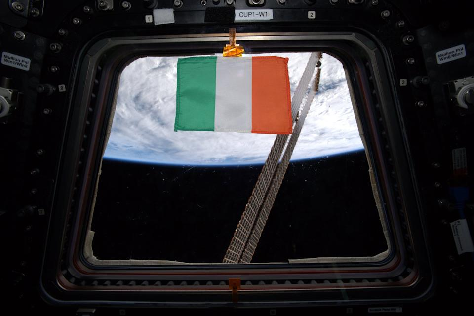 To honor St. Patrick's day at the International Space Station on March 17, 2020, NASA astronaut Andrew Morgan tweeted this photo of an Irish flag floating in one of the windows of the Cupola observatory in the orbiting lab. One of the space station's solar arrays is visible through the window, while Earth provides a cloudy backdrop. Along with this photo of the flag, Morgan tweeted a photo of Ireland, also known as the Emerald Isle, that he captured from the space station.