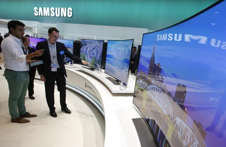 "People stand in front of Samsung's 78"" Curved UHD TV screens at the IFA consumer technology fair in Berlin"