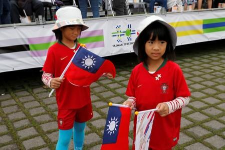 Twin girls hold Taiwanese flags before the National Day celebrations in Taipei