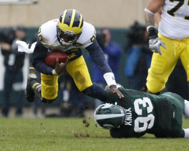 Michigan quarterback Devin Gardner, left, is tripped up by Michigan State's Damon Knox (93) during the first quarter of an NCAA college football game, Saturday, Nov. 2, 2013, in East Lansing, Mich. Michigan State won 29-6. (AP Photo/Al Goldis)