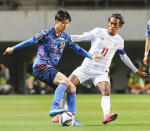 Japan's Daichi Kamada, left, controls the ball against Myanmar's Mg Mg Lwin during their Asian qualification soccer match for the FIFA World Cup Qatar 2022 at a stadium in Chiba, east of Tokyo, Friday, May 28, 2021.(Kyodo News via AP)