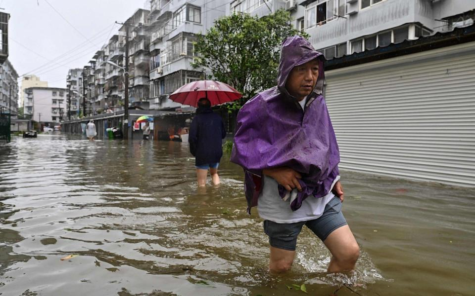 Men wade in a flooded street in a neighborhood of Ningbo, eastern China's Zhejiang province on July 25, 2021, as Typhoon In-Fa lashes the eastern coast of China - AFP