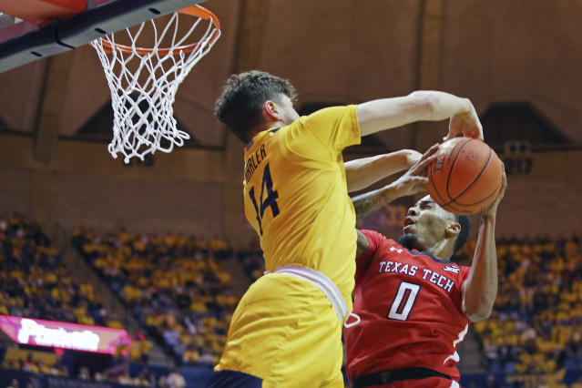 Texas Tech guard Kyler Edwards (0) goes to shoot as he is defended by West Virginia guard Chase Harler (14) during the first half of an NCAA college basketball game Saturday, Jan. 11, 2020, in Morgantown, W.Va. (AP Photo/Kathleen Batten)