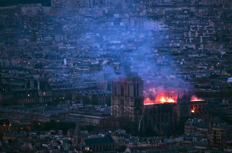 A view from Montparnasse Tower shows flames and smoke billowing from the roof of Notre Dame Cathedral in Paris. (PHILIPPE LOPEZ via Getty Images)