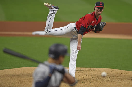 Cleveland Indians starting pitcher Shane Bieber (57) delivers to New York Yankees' Giancarlo Stanton (27) in the first inning of Game 1 of an American League wild-card baseball series, Tuesday, Sept. 29, 2020, in Cleveland. (AP Photo/David Dermer)