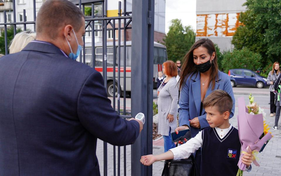 Pupils and parents have their temperature checked as they arrive at School No 58 for a festive ceremony marking the beginning of a new school year on September 1 - Vitaly Nevar/TASS