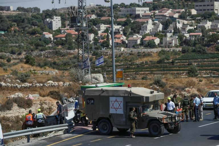 Israeli security forces gather at the scene of a reported car-ramming attack near the Jewish settlement of Elazar south of Bethlehem in the occupied West Bank