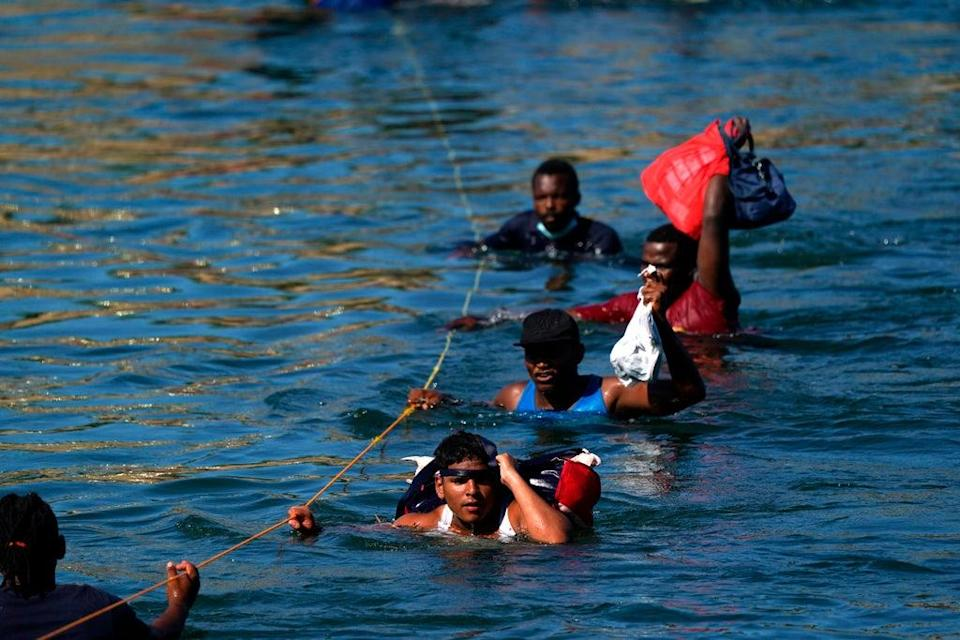 Migrants, many from Haiti, wade across the Rio Grande from Del Rio, Texas, to return to Ciudad Acuna, Mexico, Tuesday, 21 September 2021, to avoid deportation from the US (AP)