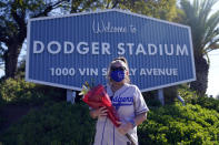 Los Angeles Dodgers fan Michelle Santisteban carries flowers to place in front of a stadium sign outside of Dodger Stadium Friday, Jan. 8, 2021, in Los Angeles. Tommy Lasorda, the fiery Hall of Fame manager who guided the Los Angeles Dodgers to two World Series titles and later became an ambassador for the sport he loved during his 71 years with the franchise, has died. He was 93. (AP Photo/Marcio Jose Sanchez)