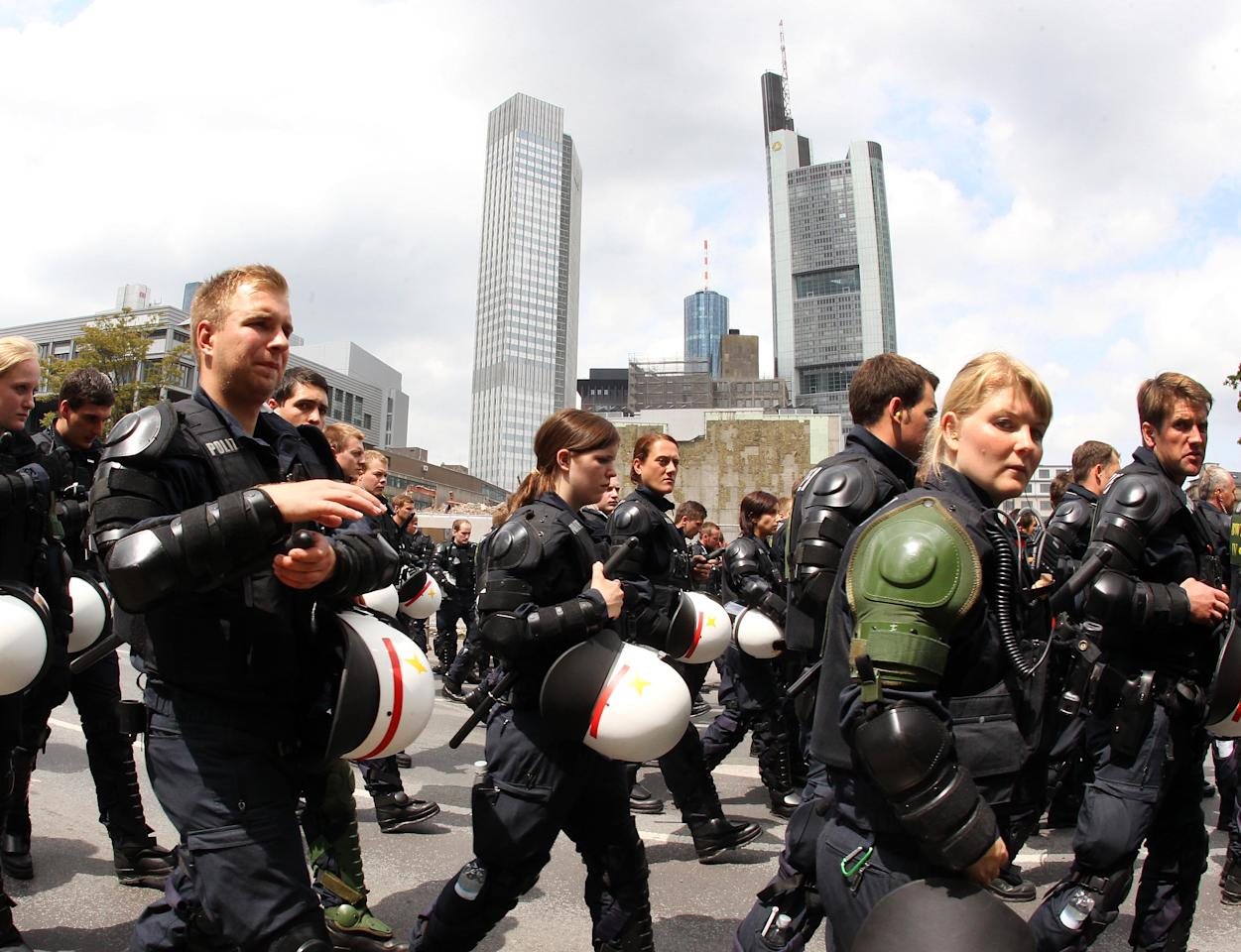 German police officers escort an anti capitalism protest march with some 20,000 people in Frankfurt, Germany, Saturday, May 19, 2012. Protesters peacefully filled the city center of continental Europe's biggest financial hub in their protest against the dominance of banks and what they perceive to be untamed capitalism, Frankfurt police spokesman Ruediger Regis said. The protest group calling itself Blockupy has called for blocking the access to the European Central Bank, which is located in Frankfurt's business district. (AP Photo/Michael Probst)