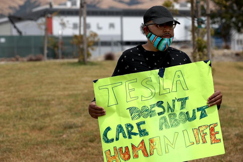 Tesla worker Carlos Gabriel holds a sign at a demonstration outside the Tesla plant in Fremont, California, on June 15, protesting working conditions there. (Photo: Justin Sullivan via Getty Images)