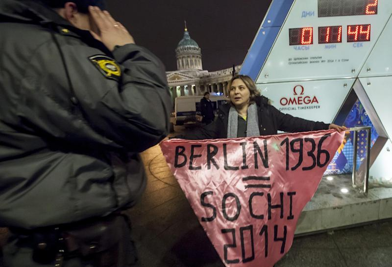 "A gay rights activist holds a banner in front of a large clock showing the number of days left until the start of the Olympic games as a police officer approaches, left, in St. Petersburg, Russia, Wednesday, Feb. 5, 2014. Russian gay rights activists protested the upcoming Olympic Games in Sochi. Two activists unfurled banners reading ""Berlin 1936 = Sochi 2014,"" referring to the Olympic Games that were held in the capital of Nazi Germany. One-man pickets are legal in Russia and the two activists holding signs were spaced far enough apart that neither was arrested. (AP Photo/Elena Ignatyeva)"