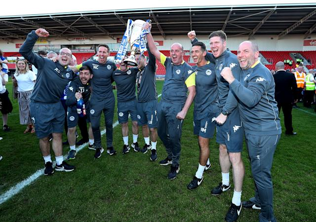 "Soccer Football - League One - Doncaster Rovers vs Wigan Athletic - Keepmoat Stadium, Doncaster, Britain - May 5, 2018 Wigan Athletic manager Paul Cook and coaching staff celebrate with the trophy after winning League One Action Images/John Clifton EDITORIAL USE ONLY. No use with unauthorized audio, video, data, fixture lists, club/league logos or ""live"" services. Online in-match use limited to 75 images, no video emulation. No use in betting, games or single club/league/player publications. Please contact your account representative for further details."
