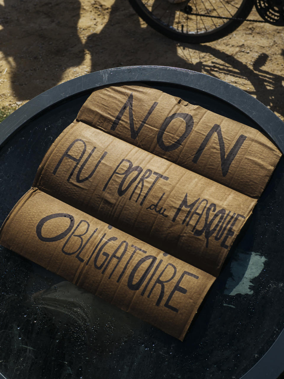 """A sign that reads: """"No to mandatory mask wearing"""", is seen on the ground during an anti-mask demonstration in Paris, Saturday, Aug. 29, 2020. A few hundred people rallied Saturday at the Place de la Nation in eastern Paris to protest new mask rules and other restrictions prompted by rising virus infections around France. (AP Photo/Kamil Zihnioglu)"""