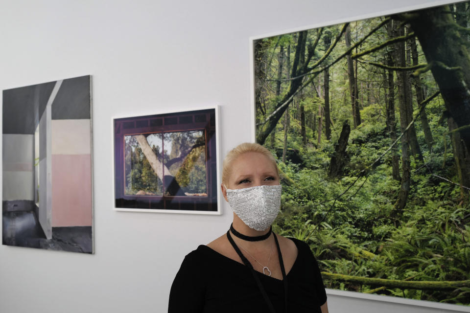 Heliante Bourdeaux-Maurin, H Gallery director, who is exhibiting at the fair, wears a protective face mask as a precaution against the coronavirus during the private view of Art Paris at the Grand Palais in Paris, Wednesday Sept. 9, 2020. Fears and restrictions over the coronavirus have caused the cancellation of all of 2020's premiere global art fairs, such as Art Basel, Frieze London, and Art Basel in Miami Beach, stymieing the main commercial artery of the multi-million-dollar industry.But organizers of Art Paris, France's second biggest contemporary art fair, have thrown caution to the wind, and are opening their doors to thousands of visitors from Thursday in the Grand Palais for a four-day show. (AP Photo/Francois Mori)