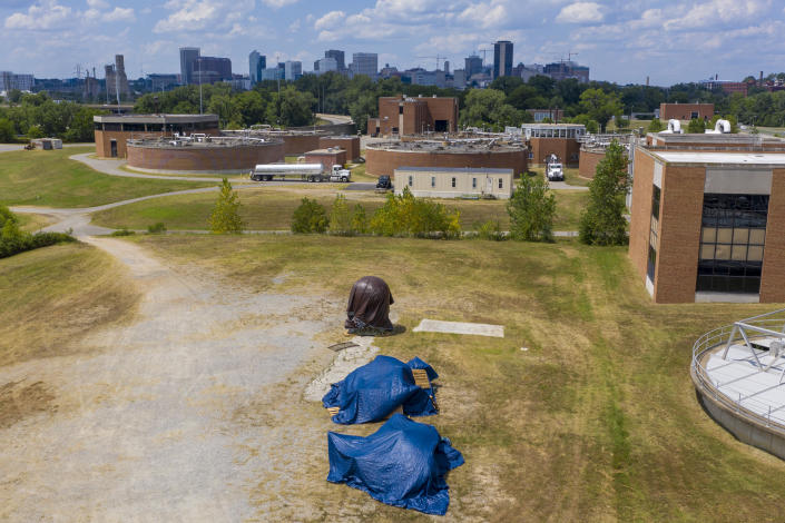 Confederate statues are covered in tarps while being stored at a waste water treatment plant near downtown Tuesday July 14, 2020, in Richmond, Va. The city of Richmond removed several of the statues along Monument Ave. where they will be stored until suitable sites can be found for them. (AP Photo/Steve Helber)